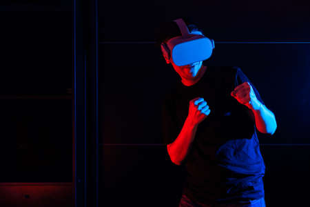 Gamer boy using virtual reality glasses having fun at home with cool lights.