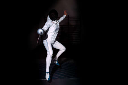 Unrecognized person wearing fencing suit and using rapier against black background.