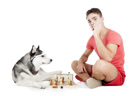 man is playing chess with a dog on a white background in the Studio photo
