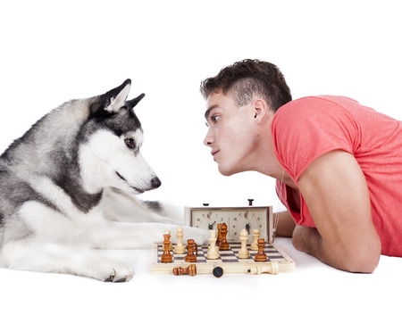 man is playing chess with a dog on a white background in the Studio Stock Photo - 23306565
