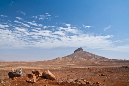 vista: Lonely hill in the endless desert of Boa Vista with blue sky in the background and huge stones in the foreground