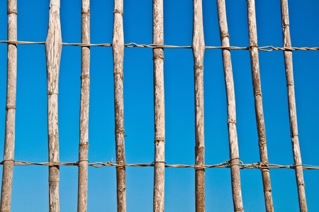 poling: Loosely fitted thatch fence with bright and clear blue sky in the background