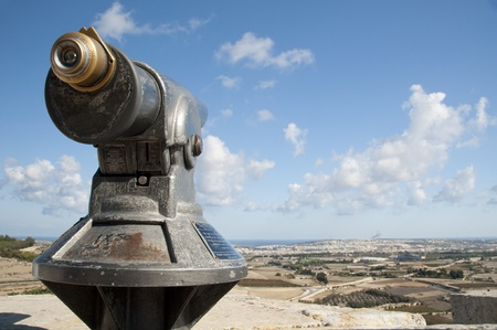 Telescope looking over the fields and houses and the sea coast on the island of Gozo Stock Photo - 13170449