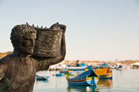 Statue of a fisherman carrying a basket full of fish with traditional luzzu boats in the background in Malta Stock Photo - 13170442