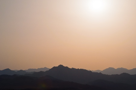 The setting sun over the hills of Dahab in Egypt photo