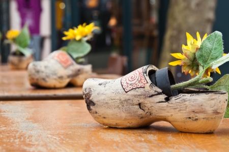 klompen: Worn-out traditional wooden shoes with sunflowers on the tables in the caf�