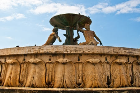Triton fountain in Valletta from a low angle with blue skies photo