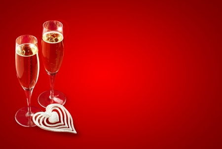 a pair of champagne glasses on red background photo