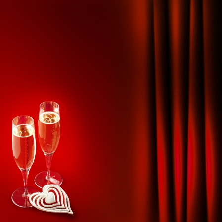 two champagne glasses with heart on red background photo