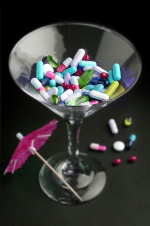 droga: cocktail di farmaci in un bicchiere su sfondo nero