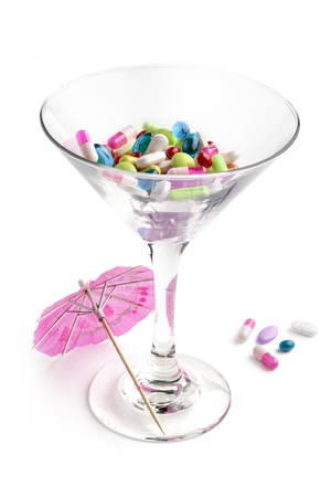 addictive: cocktail glass with medicines and paper umbrella
