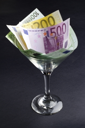 moneyed: euro banknotes in cocktail glass on black background