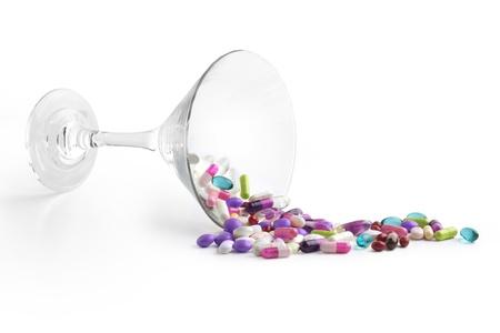 sobredosis: cóctel de vidrio con medicamentos en el fondo blanco
