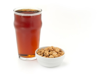 pint glass: red beer and peanuts on white background