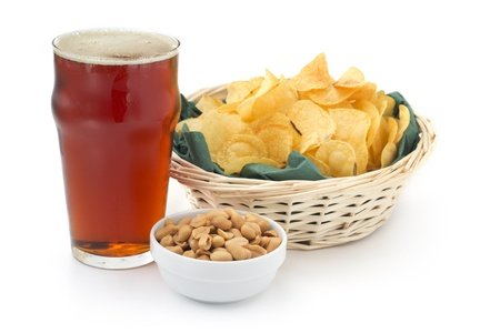 pint of red beer peanuts and chips on white background photo