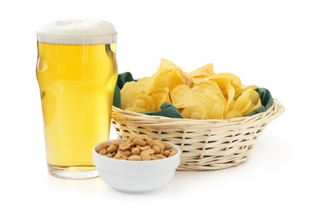 beer pint with peanuts bowl and basket of crisps photo