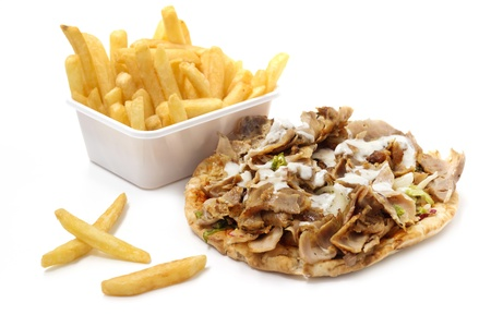 kebab with yogurt sauce and basket of fries on white background photo