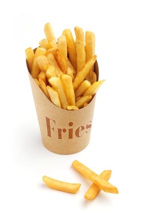 papas fritas: papas fritas francés en una envoltura de papel en el fondo blanco Foto de archivo