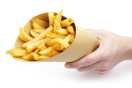 french fried potato: hand holding a funnel paper with fries