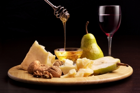 parmesan cheese, pears, honey, walnuts and wineglass Stock Photo