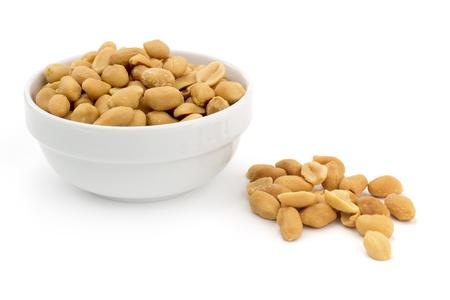 kom van geschilde pinda's op een witte achtergrond Stockfoto