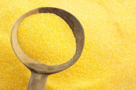 polenta: background of maize flour and wooden spoon