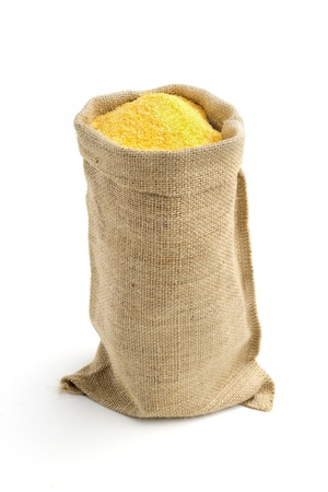 polenta: linen bag with corn flour isolated on white background