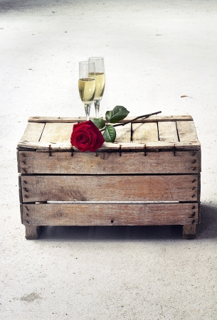 champagne glasses and red rose on a wooden case Imagens