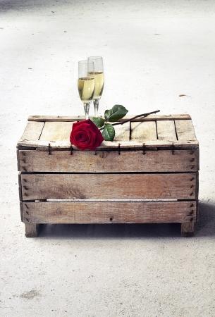 glazen champagne en rode roos op een houten kist