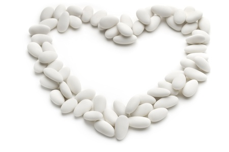 sugared almonds:  heart of sugared almonds on white background