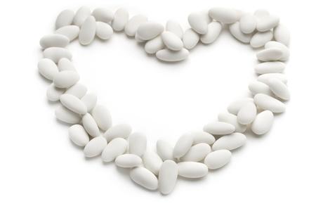 Herzen von gezuckerten Mandeln auf weißem Hintergrund Standard-Bild