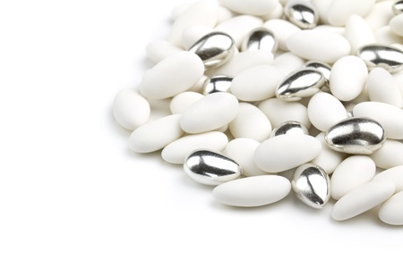 sugared: white and silver sugared almonds on white background