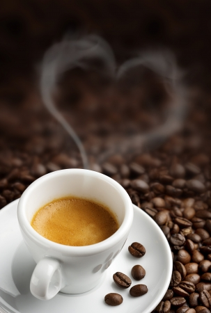 steaming: coffee cup with heart- shaped steam on background of coffee beans