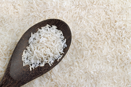 basmati:  wooden spoon with basmati rice on background of rice Stock Photo