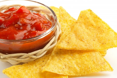 bowl of chili sauce with tortilla chips on white background photo