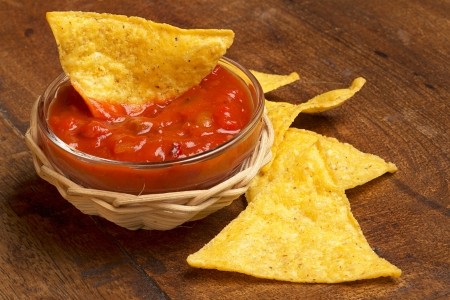 corn chip: nachos and spicy tomato sauce on wooden background