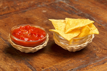 tortilla chips and spicy tomato sauce on wooden background photo