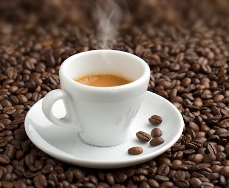 granos de cafe: humeante taza de caf� en el fondo de los granos de caf� Foto de archivo