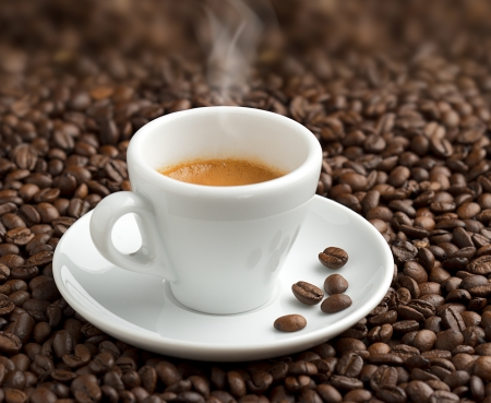 steaming cup of coffee on background of coffee beans photo