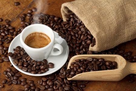 granos de cafe: taza de café con bolsa de yute y una cuchara llena de granos de café