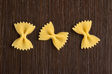 ribbon pasta: three bow tie pasta on wooden background Stock Photo
