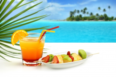 fruity salad: summer cocktail and fruit skewers on exotic seascape