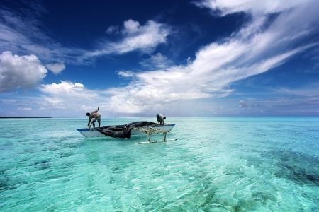 polynesia: fishermen on a canoe in a beautiful lagoon