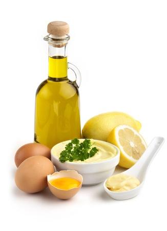 mahonesa: tazón de mayonesa y los ingredientes en el fondo blanco Foto de archivo