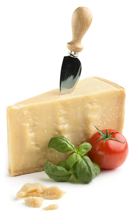 chunk of parmesan cheese with basil and tomato on white background photo
