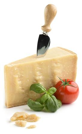 pezzo di formaggio parmigiano con basilico e pomodoro su sfondo bianco