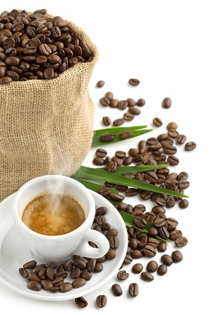 cup of coffee, jute bag and coffee beans on a green leaf