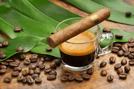 tobacco leaf: coffe cup and cigar, coffee beans and leaves on wooden background Stock Photo
