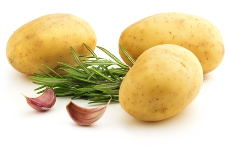 raw potatoes with rosemary and cloves of garlic photo