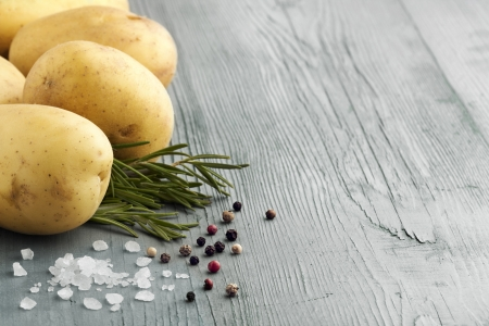 raw potatoes with rosemary, salt and pepper on a wooden table Stock Photo - 21830437